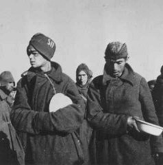 """<p><a href=""""/narrative/10135"""">Soviet prisoners of war</a> wait for food in Stalag (prison camp) 8C. More than 3 million Soviet soldiers died in German custody, mostly from malnutrition and exposure. Zagan, Poland, February 1942.</p> <p><span style=""""font-weight: 400;"""">Second only to the Jews, Soviet prisoners of war were the largest group of victims of </span><a href=""""https://encyclopedia.ushmm.org/narrative/10962/en""""><span style=""""font-weight: 400;"""">Nazi racial policy</span></a><span style=""""font-weight: 400;"""">.</span></p>"""
