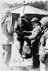 "<p>A survivor of Kaufering IV, one of the <a href=""/narrative/4391/en"">Dachau</a> subcamps in the Landsberg-Kaufering area, with US soldiers after liberation. Kaufering, Germany, after April 27, 1945.</p>"