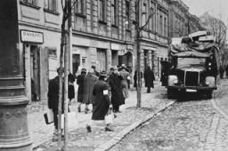 Des habitants du ghetto de Cracovie passent à côté d'un camion allemand chargé de meubles confisqués au Juifs.