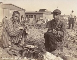 <p>Two survivors prepare food outside the barracks. The man on the right is presumed to be Jean (Johnny) Voste, born in Belgian Congo, who was the only Black prisoner in Dachau. Dachau, Germany, May 1945.</p>