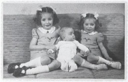 "<p>Eva, Alfred, and Leane Munzer. Infant Alfred survived in hiding; his sisters were discovered and killed in <a href=""/narrative/3673/en"">Auschwitz</a>.</p>"