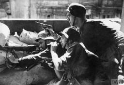 "<p>Soldiers of the Polish Home Army (Armia Krajowa) take cover behind a barricade during the <a href=""/narrative/55299"">Warsaw Polish uprising</a>. During the uprising, the Home Army was supported by 2,500 soldiers from other resistance movements, such as the National Armed Forces (Narodowe Siły Zbrojne, NSZ) and the communist People's Army (Armia Ludowa, AL). Only a quarter of the partisans had access to weapons, fighting against 25,000 German soldiers equipped with artillery, tanks, and air forces. Two of the three soldiers shown here have only small handguns. August 1944.  </p>"