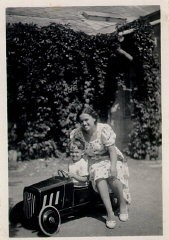 """<p>Photograph of a young <a href=""""/narrative/10475/en"""">Thomas Buergenthal</a>posing in his toy car as his mother sits alongside. 1936.</p>"""