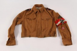 """<p><span style=""""font-weight: 400;""""><a href=""""/narrative/52091"""">Hitler Youth</a> summer uniform jacket with an armband and insignia designating the regiment and district to which the member belonged.</span></p> <p><span style=""""font-weight: 400;"""">Beginning in 1933, the Hitler Youth and its organization for girls and <a href=""""/narrative/4164"""">young women</a>, the League of German Girls, played an important role the new Nazi regime. Through these organizations, the Nazi regime <a href=""""/narrative/11357"""">indoctrinated young people</a> with Nazi ideology, including antisemitism and racism. All prospective members of the Hitler Youth had to be """"Aryans"""" and """"genetically healthy."""" Their duty was to serve <a href=""""/narrative/43"""">Adolf Hitler</a> and the <a href=""""/narrative/2529"""">Third Reich</a>. Hitler Youth boys and girls were required to wear military-style uniforms, in keeping with the """"soldierly"""" character of the Nazi Party, and conform to certain standards of behavior. Uniforms such as this one emphasized the regimented nature of the Hitler Youth.</span></p> <p><span style=""""font-weight: 400;"""">US Army soldier Arthur R. Myers obtained this uniform during his military service in <a href=""""/narrative/2388"""">World War II</a>.</span></p>"""