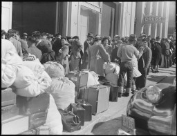 """<p><span style=""""font-weight: 400;"""">American residents of Japanese ancestry wait with their luggage for transportation during <a href=""""/narrative/32232/en"""">relocation</a>, San Francisco, California, April 6, 1942.</span></p>"""