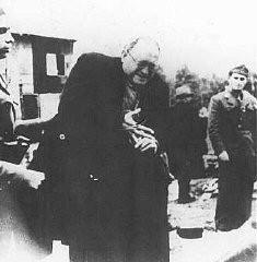 <p>اوسٹاسا (کروشیائی فاشسٹ) کیمپ کے گارڈز ایک یہودی آدمی کو گولی مارنے سے پہلے انگھوٹی اتارنے کا حکم دے رہے ہیں، جیسینوویک حراستی کیمپ، یوگوسلاویہ، 1941ء اور 1945ء کے درمیان۔</p>