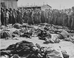 "<p>While touring the newly liberated Ohrdruf camp, General Dwight Eisenhower and other high ranking US Army officers view the bodies of prisoners who were killed during the evacuation of <a href=""/narrative/7757/en"">Ohrdruf</a>. Ohrdruf, Germany, April 12, 1945.</p>"