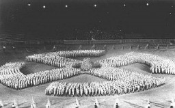At a rally, members of the Hitler Youth parade in the formation of a swastika to honor the Unknown Soldier. [LCID: 85513]