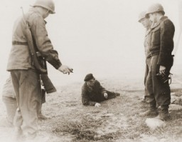 """<p>Bonde Gaza, a Hungarian musician who survived the <a href=""""/narrative/8101/en"""">Gardelegen</a> atrocity, demonstrates to American soldiers how he managed to escape from the barn which the SS had set on fire. Germany, April 14–18, 1945.</p>"""
