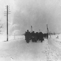 <p>Convoi de détenus juifs marchant dans la neige de la gare ferroviaire de Bauschovitz jusqu'à Theresienstadt. Tchécoslovaquie, 1942.</p>
