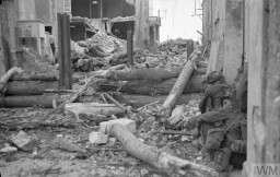 """<p>Canadian troops of the 'B' Company, North Shore (New Brunswick) Regiment take cover on June 6, 1944, or <a href=""""/narrative/2899/en"""">D-Day</a>.</p>"""