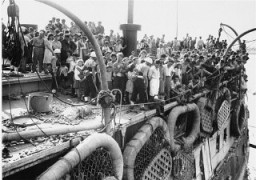 "<p>Passengers on the deck of the refugee ship <a href=""/narrative/5265/en""><em>Exodus 1947</em></a> in Haifa. British forces returned them to <a href=""/narrative/6365/en"">displaced persons</a> camps in Germany, dramatizing the plight of Holocaust survivors attempting to enter Palestine. Haifa, Palestine, July 18, 1947.</p>"