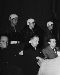 "<p>Defendants <a href=""/narrative/9811/en"">Karl Dönitz</a> (left), <a href=""/narrative/9877/en"">Erich Raeder</a> (center), and <a href=""/narrative/9908/en"">Baldur von Schirach</a> under guard in the defendants' dock at Nuremberg.</p>"