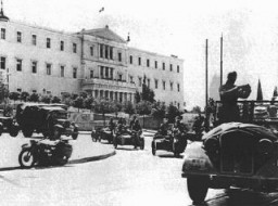 """<p>German troops drive in front of a government building during the occupation of Athensfollowing the <a href=""""/narrative/3354/en"""">invasion of the Balkans</a>. Athens, Greece, April 1941.</p>"""