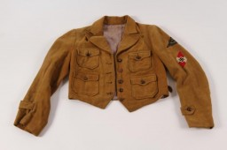"""<p><span style=""""font-weight: 400;"""">This League of German Girls jacket has two embroidered cloth patches handstitched to the upper left sleeve: a dark triangle displaying the name of the member's region, South Franconia (Süd Franken), and a Hitler Youth insignia.</span></p> <p><span style=""""font-weight: 400;"""">Beginning in 1933, the <a href=""""/narrative/52091"""">Hitler Youth</a> and its organization for girls and <a href=""""/narrative/4164"""">young women</a>, the League of German Girls, played an important role in the new Nazi regime. Through these organizations, the Nazi regime indoctrinated young people with Nazi ideology, including antisemitism and racism. All prospective members of the Hitler Youth had to be """"Aryans"""" and """"genetically healthy."""" Their duty was to serve <a href=""""/narrative/43"""">Adolf Hitler</a> and the <a href=""""/narrative/2529"""">Third Reich</a>. Hitler Youth boys and girls were required to wear military-style uniforms, in keeping with the """"soldierly"""" character of the Nazi Party, and conform to certain standards of behavior. Youth of both genders had to take part in physical exercise to prepare for their future lives in Nazi Germany. Boys engaged in military training, while the League of German Girls primed girls to be future wives and mothers. It trained girls to care for the home and family. Girls also learned skills such as sewing, nursing, cooking, and household chores.</span></p> <p><span style=""""font-weight: 400;"""">This jacket was brought back to the United States by Arthur R. Myers, a US Army soldier who participated in the Allied invasion of Nazi Germany.</span></p>"""
