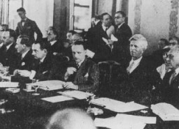 """<p>Scene during the <a href=""""/narrative/6748"""">Evian Conference</a> on Jewish refugees. On the far right are two of the US delegates: Myron Taylor and James McDonald of the President's Advisory Committee on Political Refugees. Evian-les-Bains, France, July 1938.</p>"""