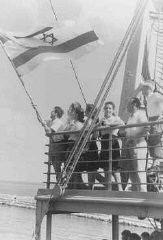 "<p>Jewish refugee children unfurl the Zionist flag as they arrive at the Haifa port aboard <a href=""/narrative/7475/en"">Aliyah Bet</a> (""illegal"" immigration) ship SS <em>Franconia</em>. Palestine, September 1945.</p>"