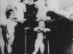 """Officiers allemands examinant des enfants polonais pour déterminer s'ils répondent aux critères """"aryens."""" Pologne, pendant ..."""