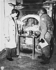 <p>After the liberation of the Flossenbürg camp, a US Army officer (right) examines a crematorium oven in which Flossenbürg camp victims were cremated. Flossenbürg, Germany, April 30, 1945.</p>
