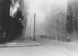 "<p>Photograph from SS General Juergen Stroop's report showing the <a href=""/narrative/2014/en"">Warsaw ghetto </a>after the German suppression of the <a href=""/narrative/3636/en"">ghetto uprising</a>. Stroop, commander of German forces that suppressed the Warsaw ghetto uprising, compiled an album of photographs and other materials. This album later came to known as ""The Stroop Report."" The right of this image from the album shows a column of Jews being transported out of the ghetto for deportation. Warsaw, Poland, April–May, 1943.</p>"