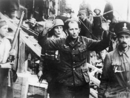 "<p>Soldiers from the Kiliński Battalion of the Polish Home Army take a German prisoner during the <a href=""/narrative/55299/en"">Warsaw Polish uprising</a>. August 20, 1944.</p>"
