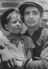 """<p>Eight-year-old Yisrael Meir (Lulek) Lau is held by a fellow <a href=""""/narrative/3956"""">Buchenwald</a> survivor, Elazar Schiff, as they arrive in Palestine aboard the RMS <em>Mataroa</em>. Haifa, Palestine, July 15, 1945.</p>"""