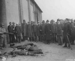 "<p>A US soldier stands guard as mayors and citizens of local towns view the corpses of inmates of the Rottleberode subcamp of Dora-Mittelbau, who were killed when the SS locked them in a barn and set it on fire. <a href=""/narrative/8101/en"">Gardelegen</a>, Germany, April 18, 1945.</p>"