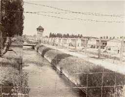 <p>View of a section of the newly liberated Dachau concentration camp as seen through the barbed-wire fence. Dachau, Germany, May 1945.</p>