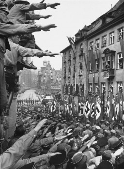 """<p class=""""document-desc moreless"""">Spectators cheer passing <a href=""""/narrative/51797"""">SA</a> formations during a Reichsparteitag (Reich Party Day) parade in Nuremberg.</p>"""