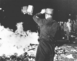 "<p>At Berlin's Opernplatz (Opera Square), an SA man throws books into the flames at the public burning of books deemed ""un-German."" This image is a still from a motion picture. Berlin, Germany, May 10, 1933.</p>"