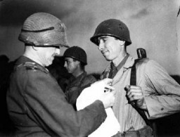 "<p>Sergeant Alexander Drabik, the first American soldier to cross the bridge at <a href=""/narrative/8160"">Remagen</a>, receiving the Distinguished Service Cross for his heroism. April 5, 1945. <a href=""/narrative/8129"">US Army Signal Corps</a> photograph taken by <a href=""/narrative/8148"">J Malan Heslop</a>.</p>"