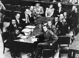 "<p>US Brigadier General Telford Taylor (front right), chief of counsel, sits at the prosecution table with his staff during the reading of charges against the defendants in the <a href=""/narrative/9532/en"">RuSHA</a> Trial. October 10, 1947.</p>"