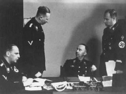 "<p><a href=""/narrative/10813/en"">Heinrich Himmler</a> (seated, center), chief of the SS, with <a href=""/narrative/10812/en"">Reinhard Heydrich</a> (standing, left), chief of the Reich Main Security Office (RSHA). Berlin, Germany, 1938.</p>"