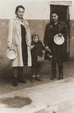 """<p>Two women and a child stand with metal bowls in front of a soup kitchen in the <a href=""""/narrative/53735/en"""">Cremona</a> displaced persons (DP) camp in Italy, 1945. Pictured are Zelda Leikach and her daughter, Masha, with their friend Hinda.</p>"""