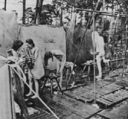<p>Peu après la libération, des survivants des camps se douchent dans des installations d'extérieur mises en place par les Britanniques. Bergen-Belsen, Allemagne, après le 15 avril 1945.</p>