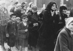 """<p>Jewish <a href=""""/narrative/3298"""">women</a> and <a href=""""/narrative/2562"""">children</a> from Subcarpathian Rus who have been selected for death at <a href=""""/narrative/3673"""">Auschwitz-Birkenau</a>, walk toward the gas chambers.May 1944.</p>"""