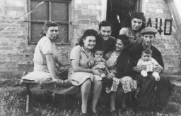 """<p>Jewish displaced persons (DPs) pose outside of a barracks in the <a href=""""/narrative/53701/en"""">Bari Transit</a> DP camp in Italy. Among those pictured are Izidor and Tauba Schachter with their baby Miriam Schachter (now Enright), on the far right, and Etta Gipsman, on the far left.</p>"""