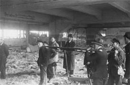 <p>Under orders of the US First Army, German civilians prepare to use a stretcher to remove corpses of victims of the Dora-Mittelbau concentration camp, near Nordhausen. Germany, April 13–14, 1945.</p>