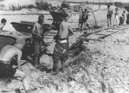 """<p>Conscripts of Hungarian Labor Service Company VIII/2 at work laying railroad track. Huszt, <a href=""""/narrative/6206"""">Hungary</a>, 1942.</p>"""