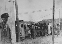 "<p>Jewish women return to the <a href=""/narrative/3182"">Kovno</a> ghetto after forced labor on the outside. They line up to be searched by German and Lithuanian guards. Kovno, Lithuania, between 1941 and 1944.</p>"