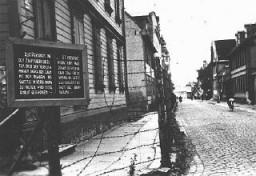 "<p>A sign, in both German and Latvian, warning that people attempting to cross the fence or to contact inhabitants of the <a href=""/narrative/6400/en"">Riga</a> ghetto will be shot. Riga, Latvia, 1941–43.</p>"