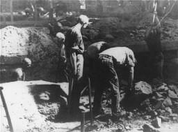 Internés au travail forcé cassant des briques avec des pioches dans la carrière du camp de concentration de Flossenbürg.