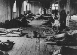 Women prisoners lie on thin mattresses on the floor of a barracks in the women's camp in the Theresienstadt ghetto. [LCID: 40228]