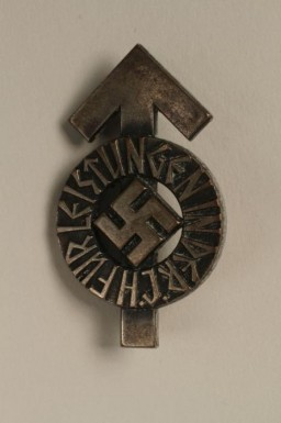"""<p>This Hitler Youth proficiency badge would have been awarded for the successful completion of a series of tests measuring physical and ideological proficiency. Success in these tests was rated according to criteria in the Hitler Youth identity document and performance book known as the <em>Leistungsbuch</em>. On this badge, the arrow shape (the tyr-rune) represents the warrior god Tyr.</p> <p>Beginning in 1933, the <a href=""""/narrative/52091"""">Hitler Youth</a> and the League of German Girls had an important role to play in the new Nazi regime. Through these organizations, the Nazi regime planned to<a href=""""https://encyclopedia.ushmm.org/narrative/11357/en"""">indoctrinate young people</a> with Nazi ideology. This was part of the process of Nazifying German society. The aim of this process was to dismantle existing social structures and traditions. The Nazi youth groups were about imposing conformity. Youth throughout Germany wore the same uniforms, sang the same Nazi songs, and participated in similar activities. Badges such as this one emphasized the paramilitary nature of the Hitler Youth organization. It was designed to train boys as future fighters and soldiers for the Nazi cause.</p>"""