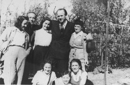 Oskar Schindler standing (second from right) with some of the people he rescued. [LCID: 03411]