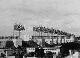 "<p>Nazi flags wave above the stadium for the Nazi Party rally grounds in Nuremberg. Architects like Albert Speer constructed monumental edifices in a sterile classical form meant to convey the ""enduring grandeur"" of the National Socialist movement. Photograph taken in Nuremberg, Germany, between 1934 and 1936. </p>"