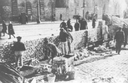 <p>وارسا کی یہودی بستی کے گرد یہودی افراد ایک دیوار کی تعمیر پر کام کررہے ہیں۔ اکتوبر 1940 میں جرمنوں نے یہودی بستی کی تعمیر کا اعلان کیا اور نومبر 1940 میں یہودی بستی کو باقی وارسا سے الگ کردیا گيا۔</p>