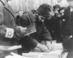 <p>پھیری والے پرانی عبرانی کتابیں بیچ رہے ہیں۔ وارسا یہودی بستی، پولینڈ، فروری 1941 ۔</p>
