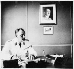 "<p>The commandant of <a href=""/narrative/6074/en"">Gross-Rosen</a>, SS-Obersturmbannfuehrer Arthur Roedl, at his desk with a photograph of Adolf Hitler hanging on the wall. Gross-Rosen, Germany, 1941.</p>"