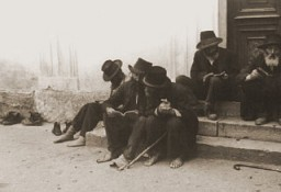 "<p>Jewish men sitting on the steps of a synagogue. <a href=""/narrative/7590/en"">Munkacs</a>, Czechoslovakia, 1936.</p>"